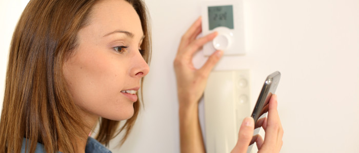 PRO-woman-regulating-thermostat-with-smartphone