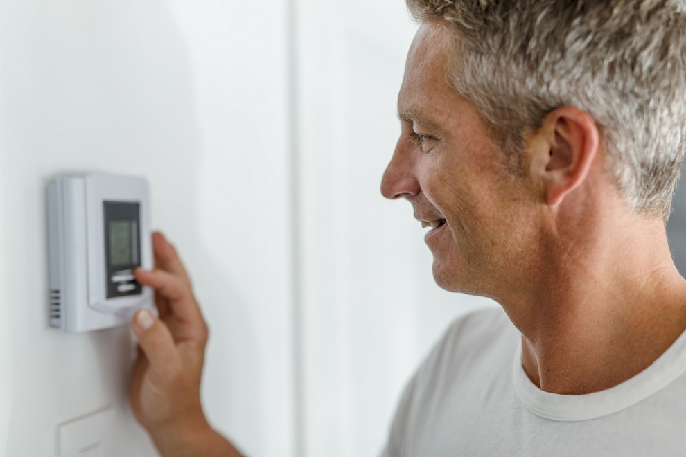 Man Adjusting Heating System in Home