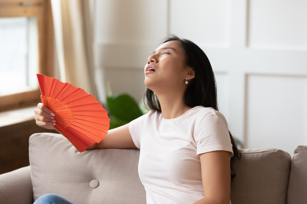 Lady fanning herself due to hot spot in room (How to Avoid Hot and Cold Spots in your Home)